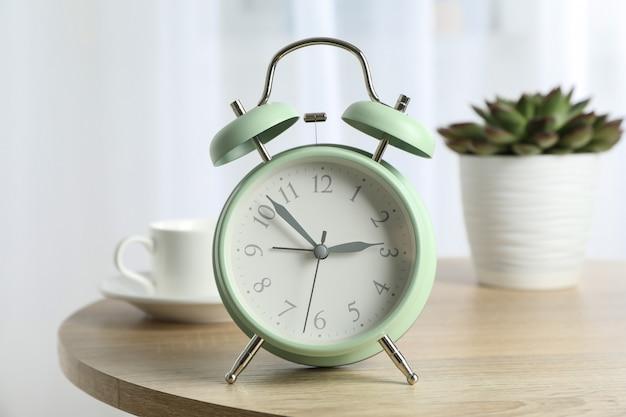 Bella retro sveglia con la tazza di caffè e la pianta succulente sulla tavola contro luce