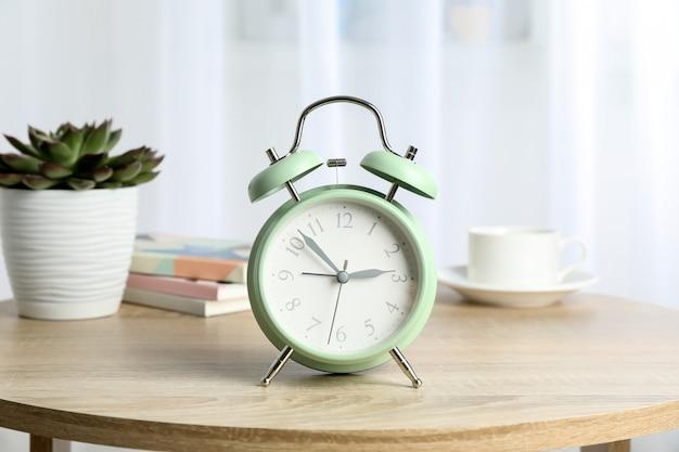 Bella retro sveglia con la tazza di caffè, la pianta succulente e i libri sulla tavola contro luce