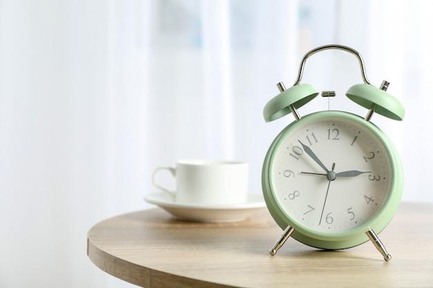 Bella retro sveglia con la tazza di caffè sulla tavola contro luce