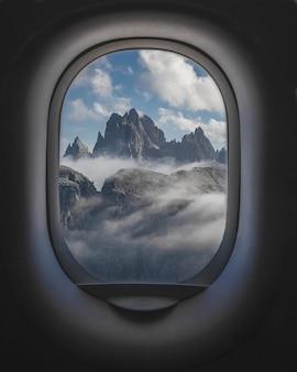 Bella ripresa di montagne e un cielo nuvoloso dall'interno dei finestrini degli aerei