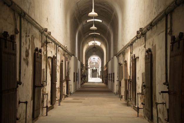Bella ripresa di un corridoio ad arco in un vecchio edificio abbandonato con molte porte