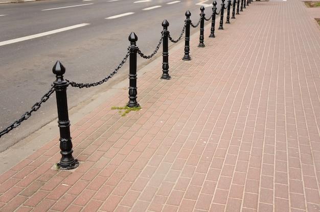 Bella ripresa di un marciapiede in mattoni con pali metallici di sicurezza moderni neri