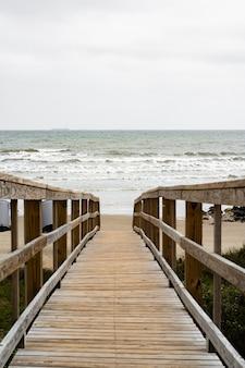 Bella ripresa di una passerella in legno sulla spiaggia