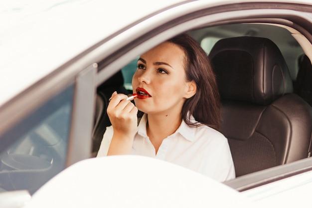 Bella riuscita giovane donna castana elegante che dipinge le sue labbra con rossetto rosso in automobile