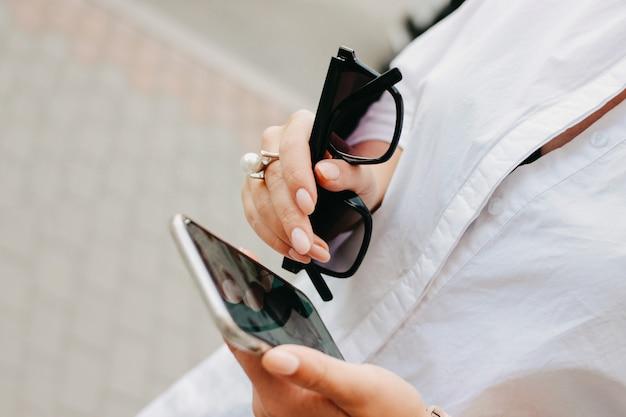 Bella riuscita giovane donna elegante con gli occhiali da sole e il telefono cellulare in sue mani