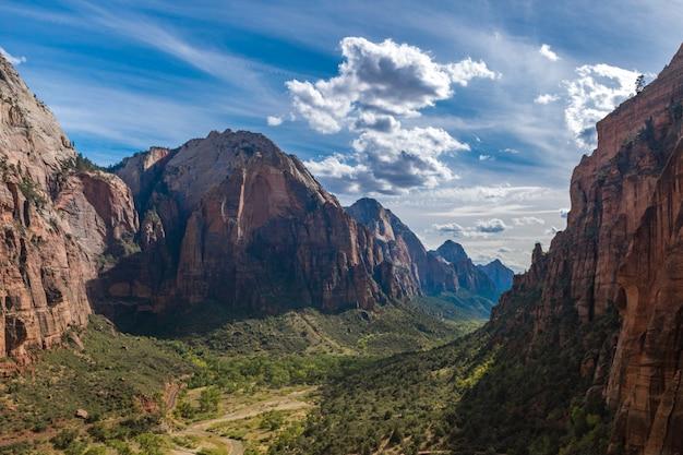 Bella scena di un canyon verde circondato da rocce sotto un cielo estivo luminoso