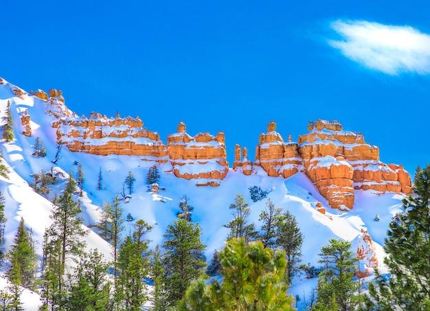 Bella scogliera rocciosa ricoperta di neve con l'incredibile cielo blu chiaro