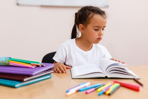 Bella scolara elementare che studia nell'aula