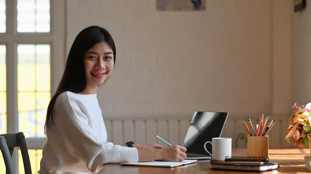 Bella scrittrice seduta al tavolo di lavoro e scrivendo la sua nuova fiction sul taccuino di fronte al suo tablet nero schermo vuoto, tornando alla fotocamera e sorridendo. stile di vita femminile.