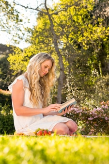 Bella seduta bionda sulla lettura dell'erba nel giardino