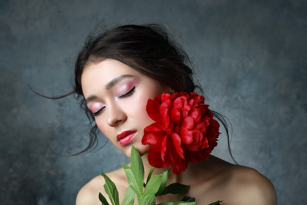 Bella sexy elegante giovane adulto in abito elegante con bel bouquet di peonie rosa. studio ritoccato