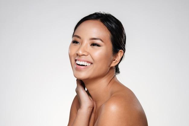 Bella signora asiatica sorridente che osserva da parte