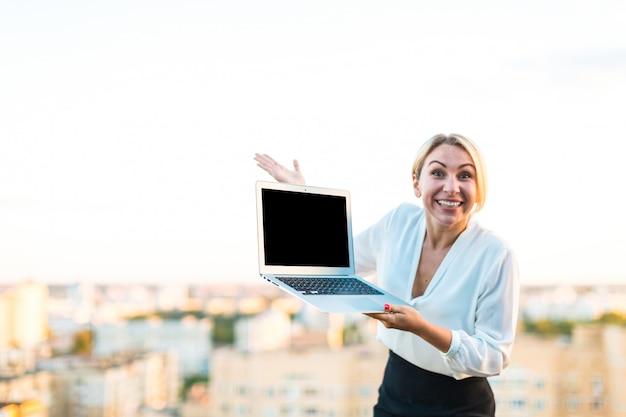Bella signora astuta di affari che sta sul tetto con il computer portatile in mani, mostra il computer portatile vuoto