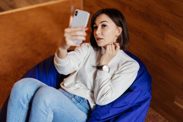 Bella signora bruna in blue jeans e t-short bianco fa selfie avere una videocall sul suo telefono
