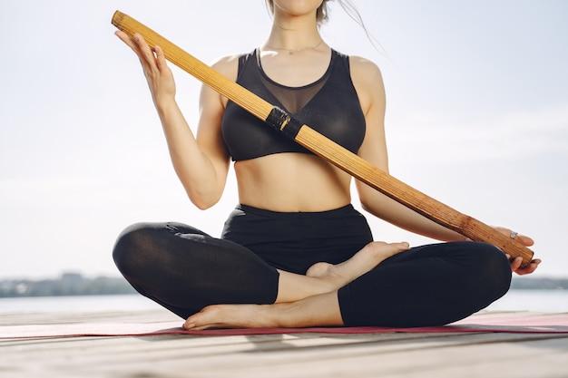 Bella signora che si allena in un parco estivo. bruna che fa yoga. ragazza in una tuta sportiva.