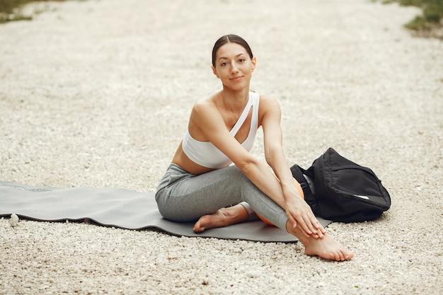 Bella signora che si allena su una spiaggia estiva. bruna che fa yoga. ragazza in una tuta sportiva.
