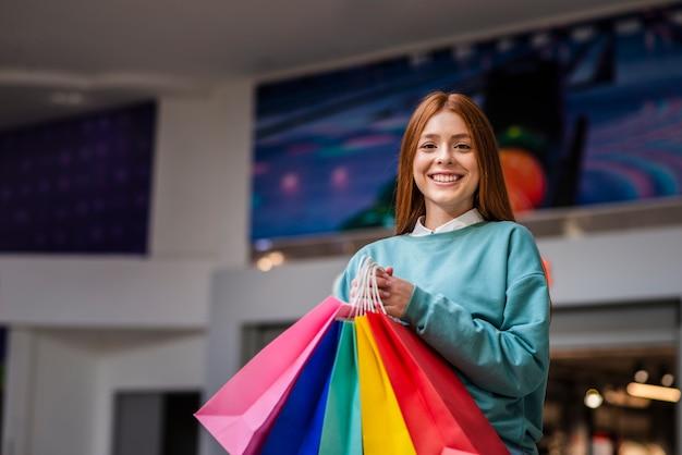Bella signora che tiene i sacchetti della spesa variopinti