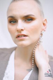 Bella signora che tiene il suo collo e che osserva in vestito bianco e grigio durante il giorno.
