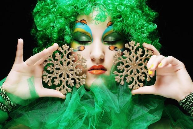 Bella signora con trucco artistico che tiene il decoratio di natale