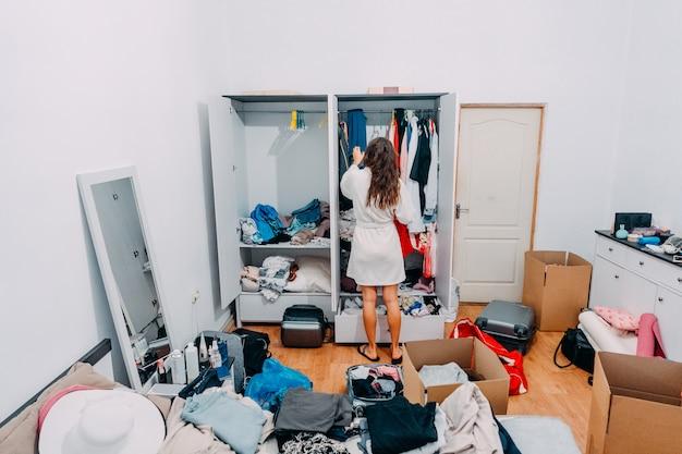 Bella signora dall'aspetto moderno nell'appartamento moderno si prepara al viaggio