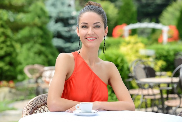 Bella signora in abito colorato, bere il caffè.