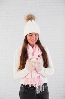 Bella signora in guanti, cappello bobble e sciarpa con tazza e caramelle