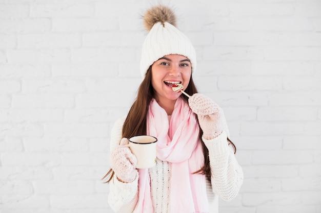 Bella signora in guanti, cappello bobble e sciarpa con tazza e lecca-lecca