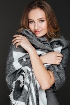 Bella signora in posa vestita in sciarpa plaid