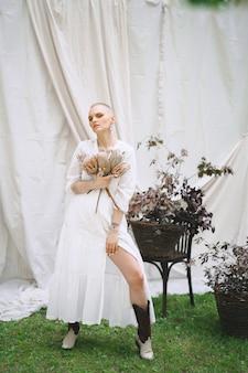 Bella signora nella condizione bianca e grigia del vestito e nelle decorazioni della tenuta in giardino con la parete bianca durante il giorno.