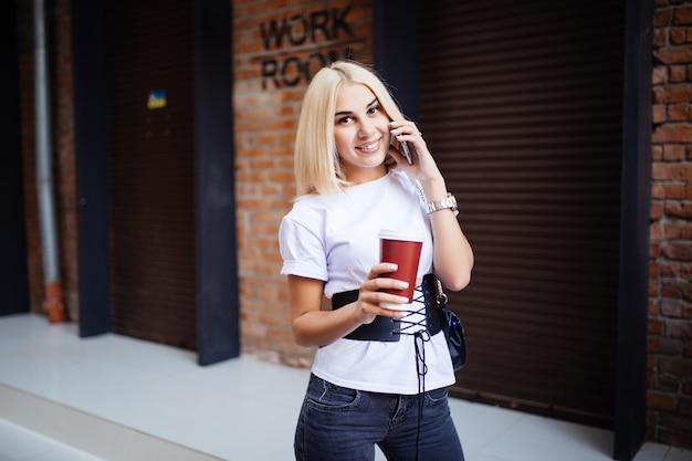 Bella signora ragazza femminile che beve caffè americano e parla al telefono. capelli biondi della donna vicino al muro di mattoni