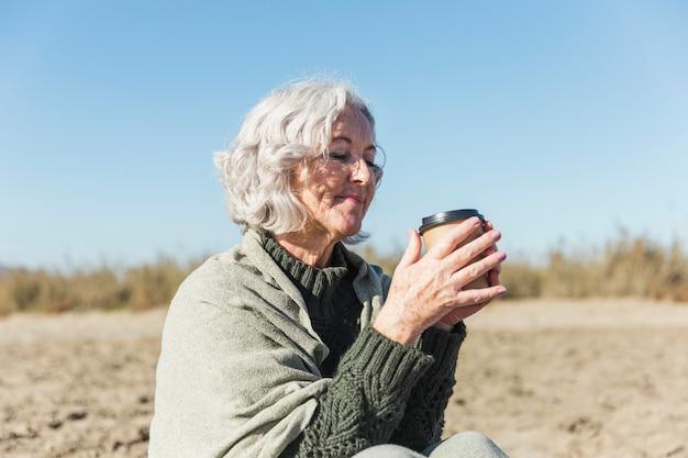 Bella signora senior tenendo il caffè