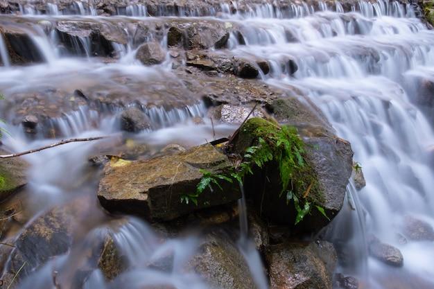 Bella soffice cascata con roccia.