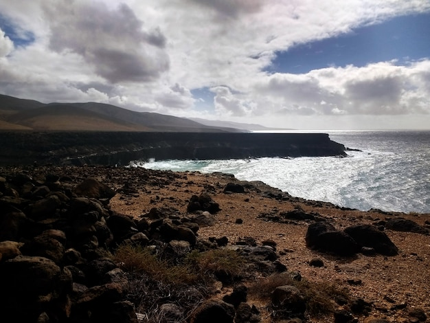 Bella spiaggia di sabbia a fuerteventura, spagna ricoperta di rocce