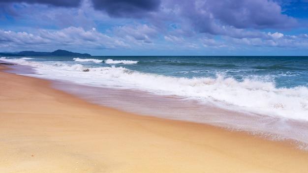 Bella spiaggia sabbiosa tropicale con l'oceano blu e la priorità bassa del cielo blu
