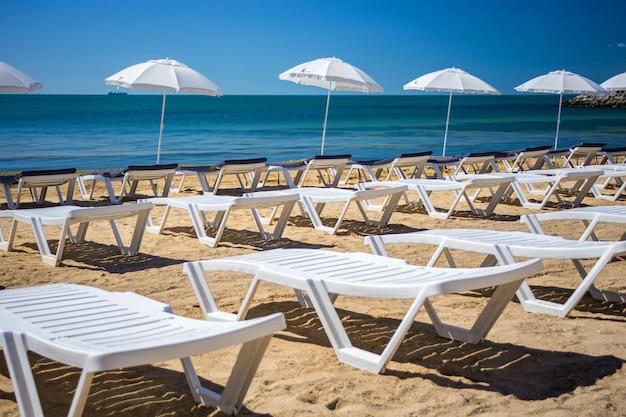 Bella spiaggia vuota con file di lettini sotto gli ombrelloni di paglia