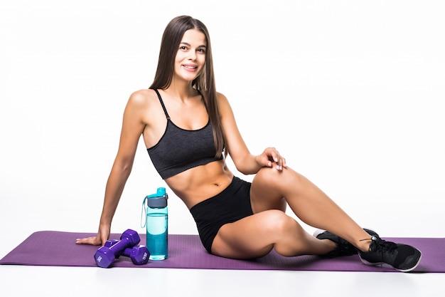 Bella sportiva stanca con la bottiglia di acqua mentre riposando sul pavimento isolato su gray
