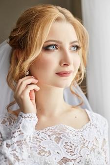 Bella sposa bionda al mattino in un abito da sposa bianco con velo sulla sua testa, ritratto della sposa prima della cerimonia di nozze. esperienza delle spose prima del matrimonio