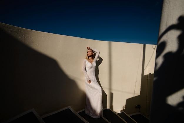 Bella sposa bionda in fuga in abito da sposa bianco sull'isola di santorini in grecia con vista mozzafiato