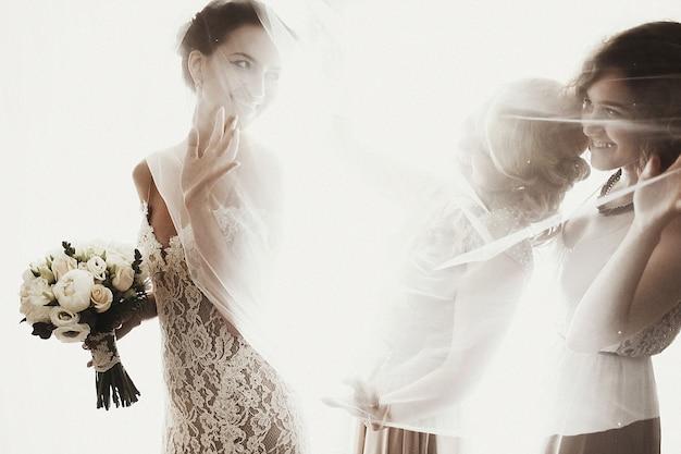 Bella sposa bruna sessuale in abito bianco con damigelle d'oro vicino alla finestra