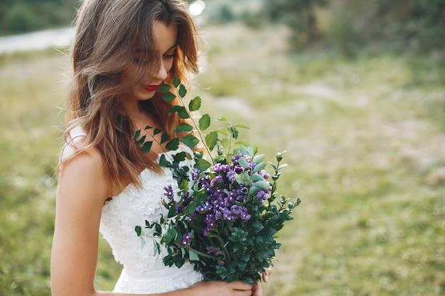 Bella sposa che cammina in un campo estivo