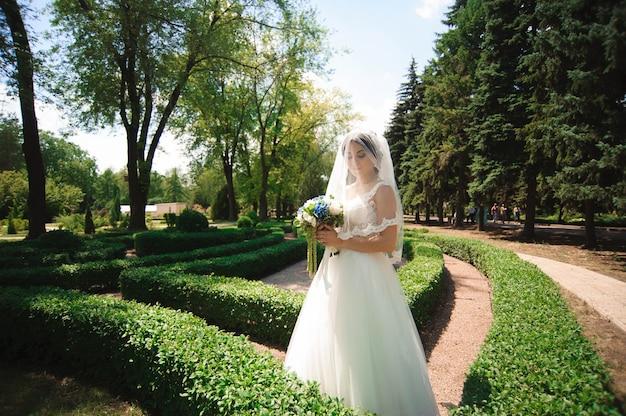 Bella sposa con bouquet di fiori da sposa, donna attraente in abito da sposa. felice donna appena sposata. sposa con trucco sposa e acconciatura. sposa sorridente. giorno del matrimonio. matrimonio.
