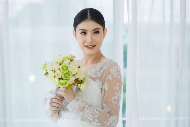 Bella sposa con bouquet di fiori da sposa