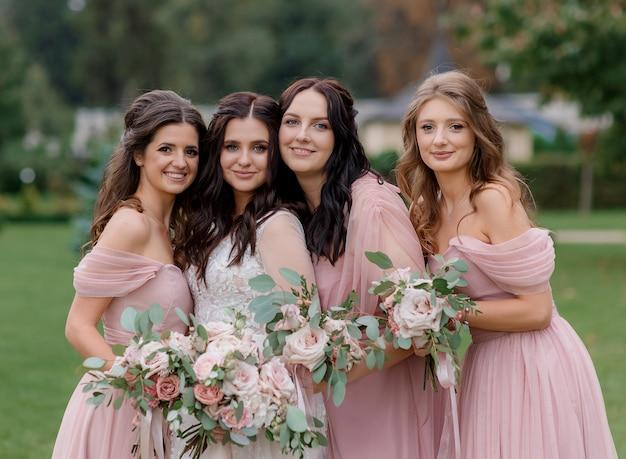 Bella sposa con damigelle vestite in abiti rosa stanno tenendo mazzi di fiori rosa pallido fatti di rose all'aperto
