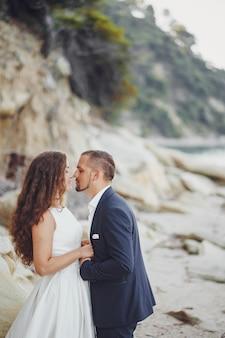 Bella sposa dai capelli lunghi in abito bianco con il marito sulla spiaggia vicino a grandi pietre