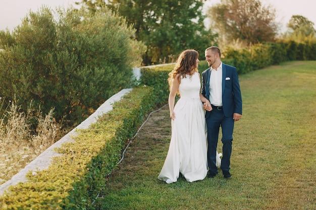 Bella sposa dai capelli lunghi in abito bianco con il suo giovane a piedi nella natura