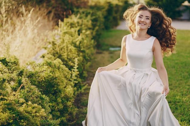 Bella sposa dai capelli lunghi in un magnifico abito bianco a piedi nella natura