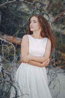 Bella sposa dai capelli lunghi in un magnifico abito bianco in natura