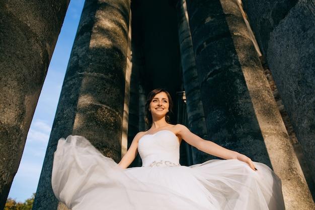 Bella sposa felice in abito da sposa bianco tra le colonne giganti della chiesa