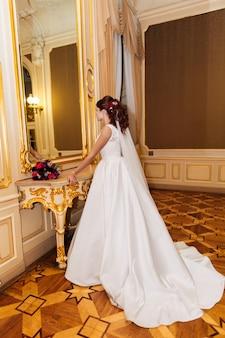 Bella sposa guardarsi allo specchio in casa, foto nel castello