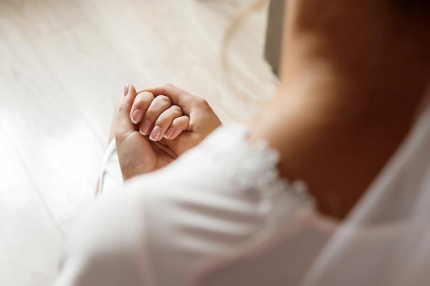 Bella sposa in abito a maniche lunghe sta guardando la sua manicure